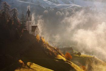 Originální fotoobraz kostelíka v oblasti Alta Badia v Dolomitech při podzimním mlhavém ránu v údolí La Valle