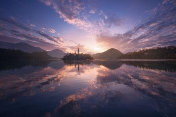 Nádherné mraky nasvícené ranním sluncem a zrcadlící se v klidné hladině jezera Bled ve Slovinsku - Julské Alpy.