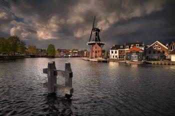 Podvečerní pohled na větrný mlýn v centru města Haarlem, když se na město hnala jarní bouře - Severní holandsko, Nizozemsko.