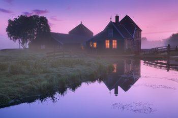 Typický dřevěný venkovský dům u vodního kanálu v mlhavé krajině Severního Holandska, Nizozemsko.
