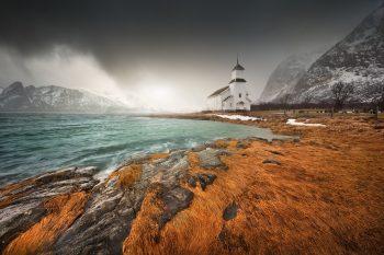 Kostelík na pobřeží Lofot těsně před sněhovou bouří