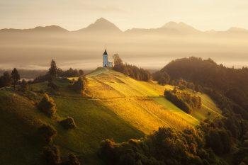 Horský kostel Jamník v pozadí s horskými štíty Julských Alp - Slovinsko.