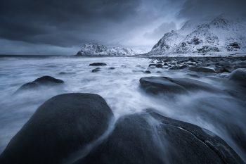 Kamenitá pláž Uttakleiv na pobřeží Lofot v severní části Norska