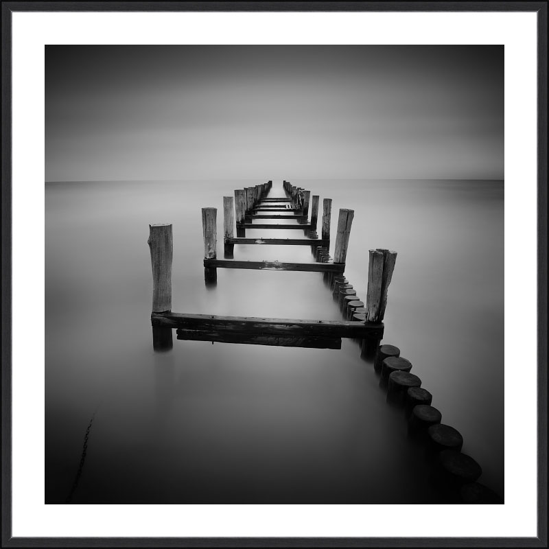 Černobílý minimalistický fotografický obraz Opuštěné molo z divokého pobřeží Baltu je v černém rámu s bílou paspartou decentním prvkem pro každou stěnu..