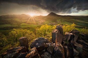 Jarní bouřkový západ slunce na zřícenině hradu Ostrý v Českém středohoří s výhledem na Milešovku.