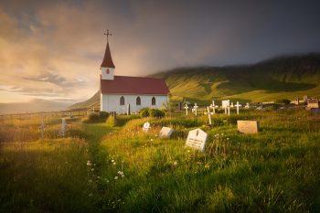 Typický Islandský kostel Reyniskirkja s hřbitovém při západu slunce v oblasti Vík na jižním pobřeží Islandu