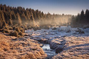 Jeden z přítoku vodní nádrže Fláje s dřevěnou lávkou při mrazivém podzimním východu slunce v Krušných horách.