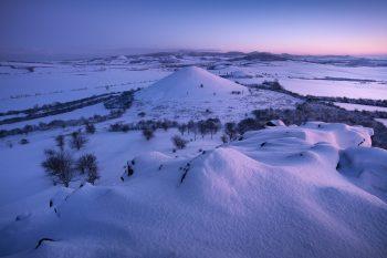Výhled ze zasněžených Křížových vršků na Malý vrch a Šibeník před východem slunce při mrazivém ránu v zimním Českém středohoří.