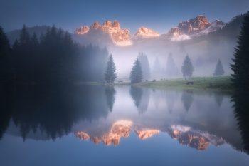 Horské zasněžené štíty se zrcadlí v malebném malém horském jezírku v Rakouských Alpách u Salzburgu