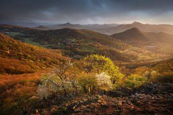 Výhled do širokého údolí s rozkvetlými stromy v jarním Českém středohoří nedaleko Liroměřic.