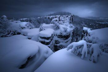Zamračené mrazivé ráno v Tisé. Pohled z hlavní vyhlídky na čerstvě zasněžené skalní město v srdci chráněné krajiné oblasti Labské pískovce nedaleko Děčína.