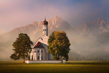 Fotoobraz kostelu St. Coloman v pozadí s horskými štíty bavorských Alp poblíž zámku Neuschwanstein