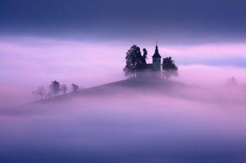 Kostelík Sveti Tomaž vystupující z ranní mlhy při podzimním focení ve Slovinsku