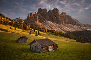 Malebné údlí Val di Funes se starými dřevěnými sruby při podzimním západu slunce na fotoobrazu z Dolomit
