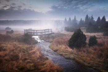 Mlhavý podzimní večer u meandru horského potoka s dřevěnou lávkou v Krušných horách.
